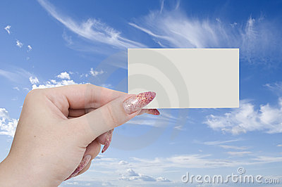 Card in a hand on sky background