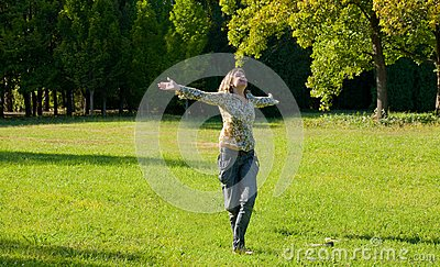 Carefree adorable girl with arms out in field.