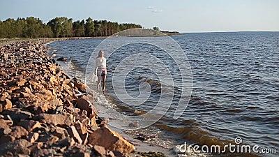 Carefree beautiful woman strolling seashore stock footage