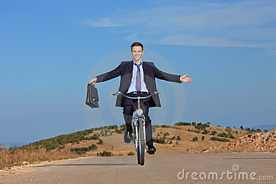 Carefree businessman riding a bicycle