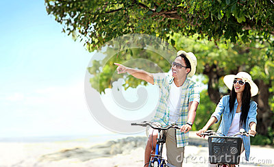 Carefree couple having fun and smiling riding bicycle at the bea