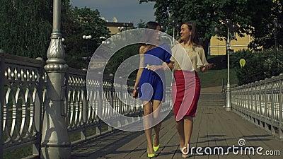 Carefree elegant women walking on bridge in spring stock video