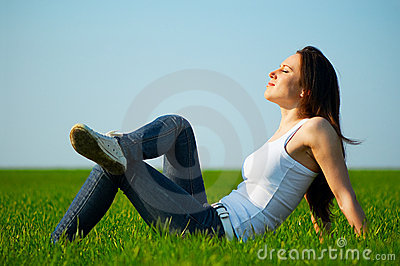 Carefree girl sitting at the field