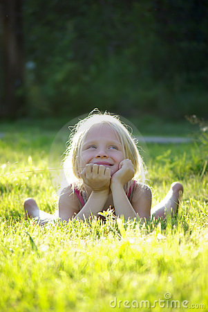 Carefree joyful little girl on gras