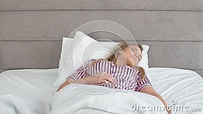 carefree livstid Nätt flicka som vaknar upp på säng i morgon arkivfilmer