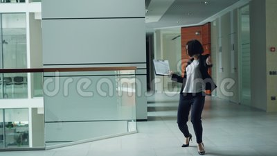 Carefree office worker is dancing in lobby holding paper then throwing folder away and relaxing moving body. Modern. Carefree female office worker is dancing in stock video footage