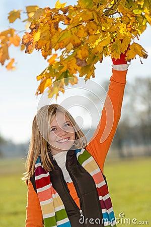Carefree teen girl picking leaves fall playing