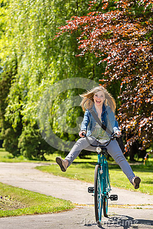 Carefree teenager riding bicycle across the park