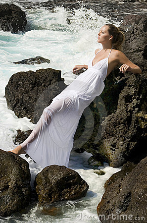 Carefree woman in white dress in the ocean