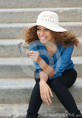 Carefree young woman laughing outdoors
