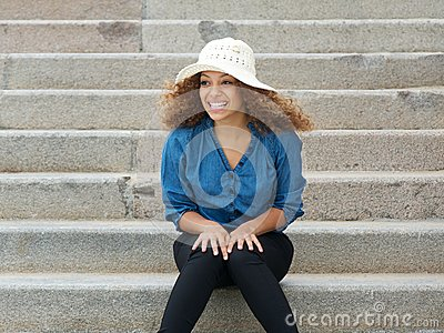 Carefree young woman wearing hat sitting on stairs