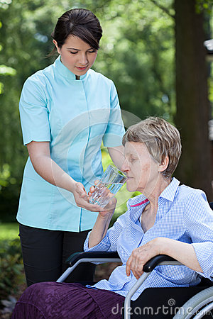 Caregiver giving glass of water to senior woman