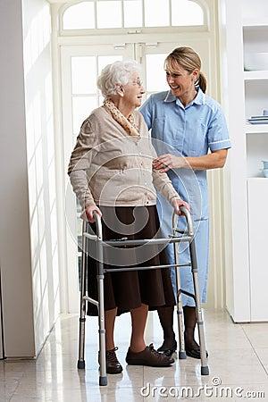 Carer Helping Elderly Senior Woman Using Walking F