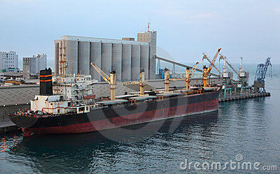 Cargo ship docked to industrial port