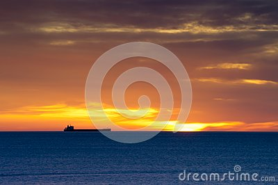 Cargo ship on horizon at dawn