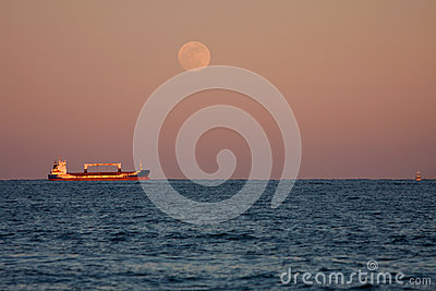 Full Moon Shines On Anchored Cargo Ship