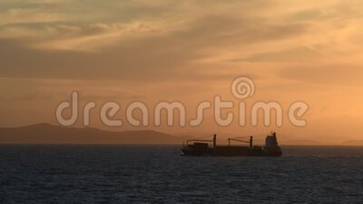 Cargo Ship at Sunset. A cargo ship at sunset in Silhouette. Camera handheld stock video