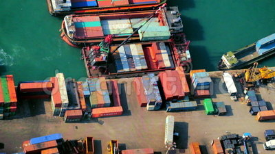 Cargo ships loaded by crane with cargo containers at a busy port terminal. Hong Kong. HONG KONG - JAN 23, 2015: Cargo ships loaded by crane with cargo containers stock footage