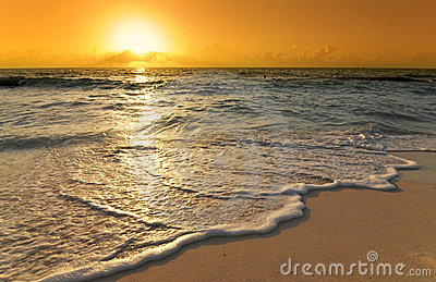 Caribbean sunrise with wave on beach