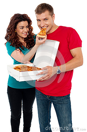 Caring girlfriend making her boyfriend eat pizza