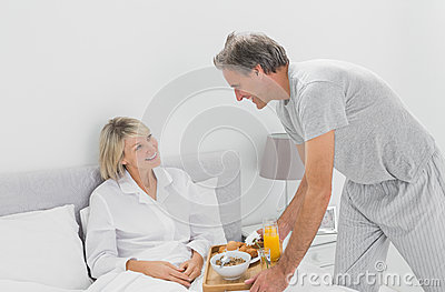 Caring man bringing breakfast in bed to his partner