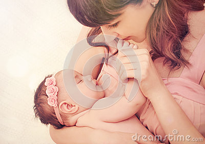 Caring mother kissing fingers of her cute sleeping baby girl Stock Photo