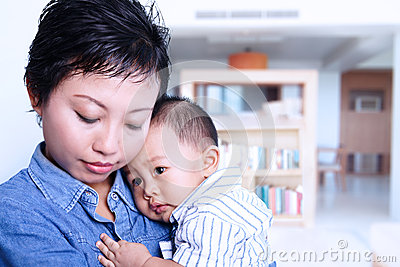 Caring mother nursing baby at home