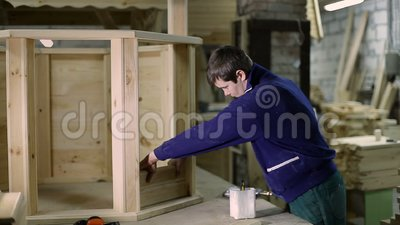 Carpenter applying glue on wooden plank with brush stock footage