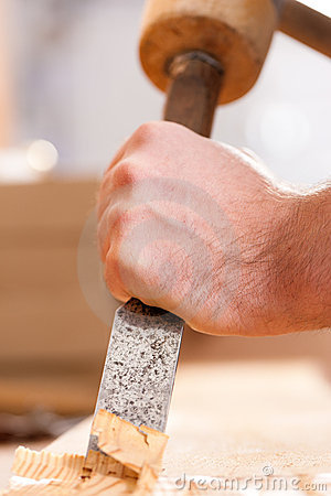 Carpenter with chisel and hammer