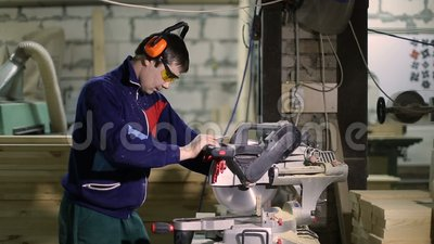 Carpenter cutting wood with sliding mitre saw stock footage