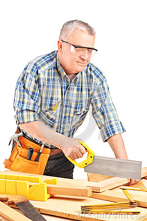Carpenter cutting wooden batten with a saw