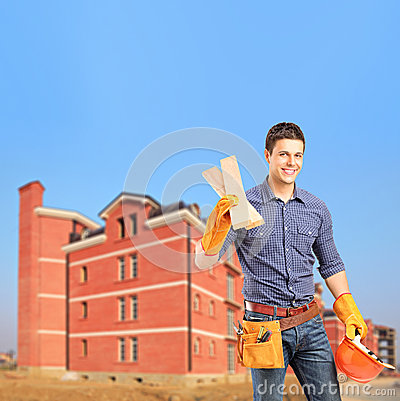 Carpenter holding sills with an apartment block