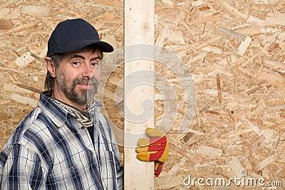 Carpenter holds a plank