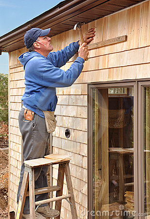 Carpenter installing cedar shingles