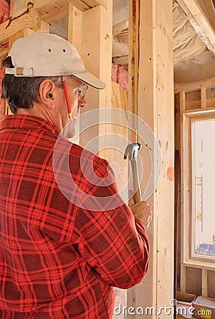 Carpenter pounding nail into interior wall