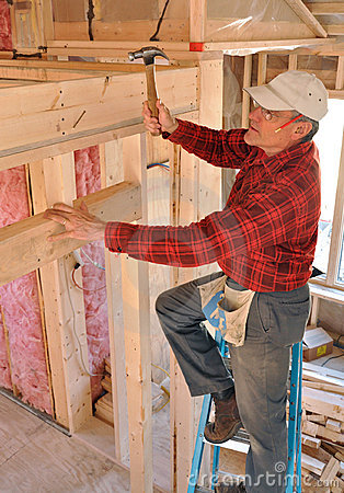 Carpenter pounding nail into interior wall