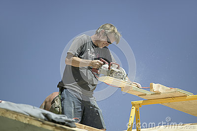 Carpenter sawing board on roof Editorial Stock Photo
