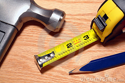 Carpenter Tools Hammer and Tape Measure on Wood