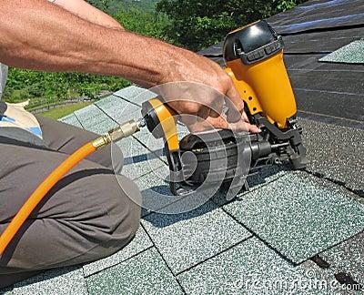 Carpenter uses nail gun to attach asphalt shingles