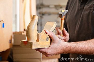 Carpenter with wood planer and hammer