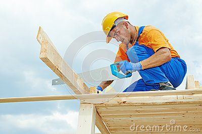 Carpenter works with hand saw