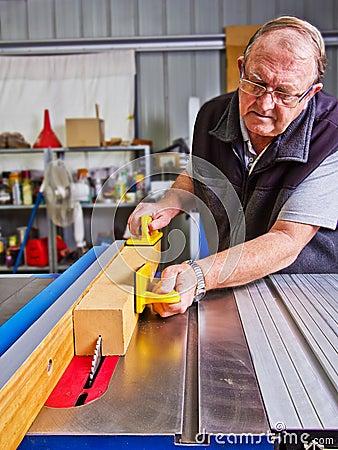 Carpintero de sexo masculino mayor que usa un banco de la sierra