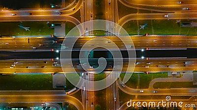 Carretera y puente grande con cruce de caminos iluminado por linternas en la noche, marcas en asfalto son visibles, parte aérea n almacen de metraje de vídeo