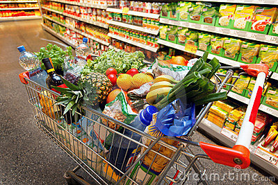 Carro de compras con la fruta en supermercado