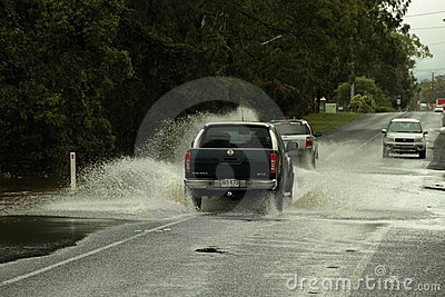 Cars crossing flooded road Editorial Image