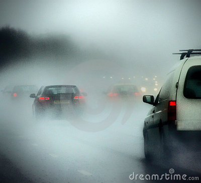 Cars on a road in heavy rain and fog