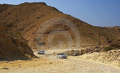 Cars on a rocky rough road in a wadi