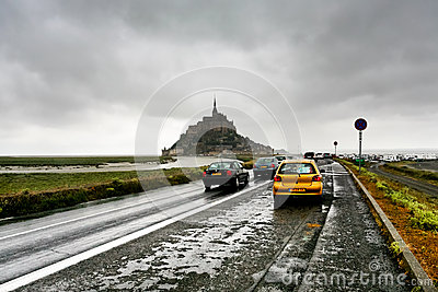 Cars on wet road and Mont Saint-Michel, France Editorial Stock Photo
