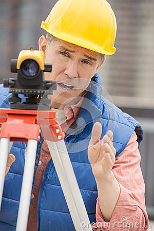 Cartographer Gesturing While Using Theodolite