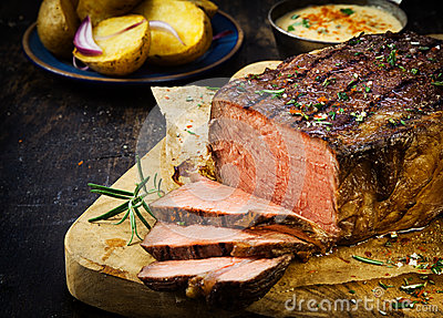 Carved rare roast beef seasoned with herbs